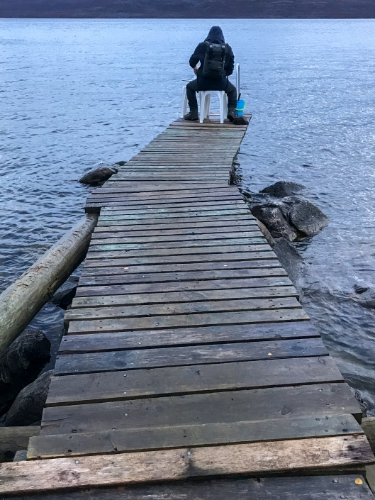 man sitting at the end of a wooden pier over the lake at dusk