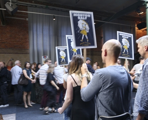 group of people, some holding banners of salt